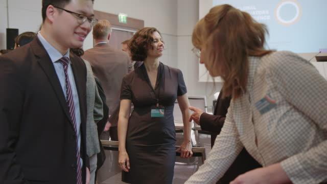 führungskräfte diskutieren vor seminar im hotel - konferenz stock-videos und b-roll-filmmaterial