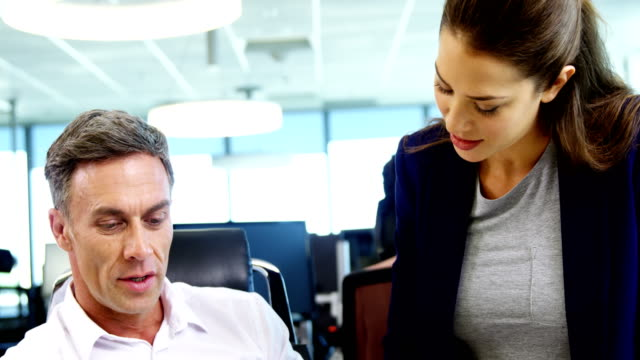 Executives discussing over laptop in office video