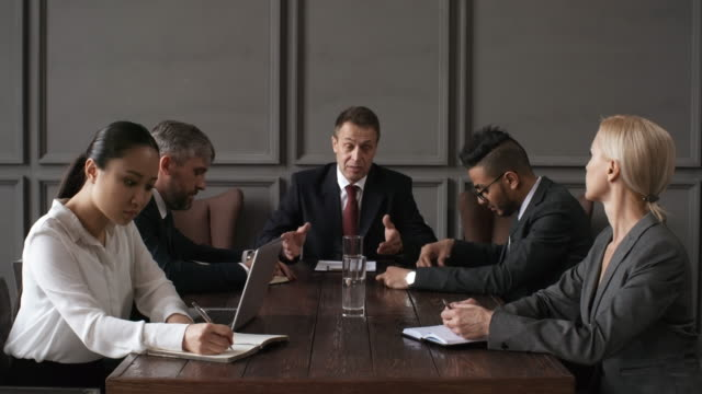 Executives Listening to CEO at Private Meeting Waist-up shot of company executive board members participating in business meeting and sitting around table listening to Caucasian male CEO, while secretary in white blouse is trying to take minutes chair stock videos & royalty-free footage
