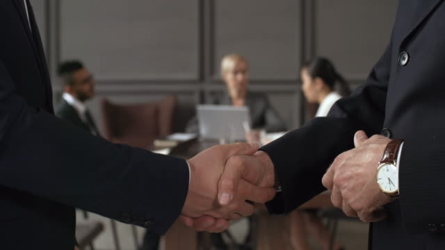 Executives Shaking Hands during Corporate Meeting