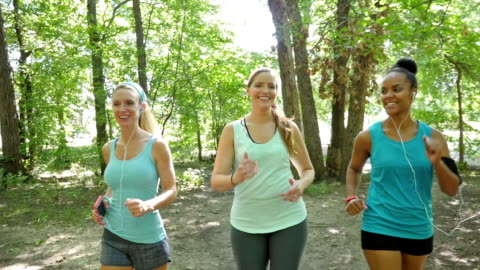 Exercise club power walking together outdoors on dirt trail Group or exercise club of young and mid adult women is exercising together in wooded park. They are smiling and talking while they walk or power walk on dirt path surrounded by green trees. They are wearing athletic clothing, and using smart phones and mp3 players with headphones to listen to music. footpath stock videos & royalty-free footage