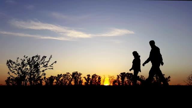 Ejercicio de la puesta del sol en el país Silueta hombre y de la mujer - vídeo