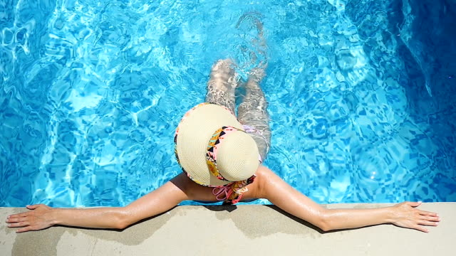 Exercising legs & relaxation in pool Slow motion video of pretty woman enjoying summer sunbathing & relaxation in pool. Carefree woman kicking the pool water, exercising and having tranquil day. swimwear stock videos & royalty-free footage