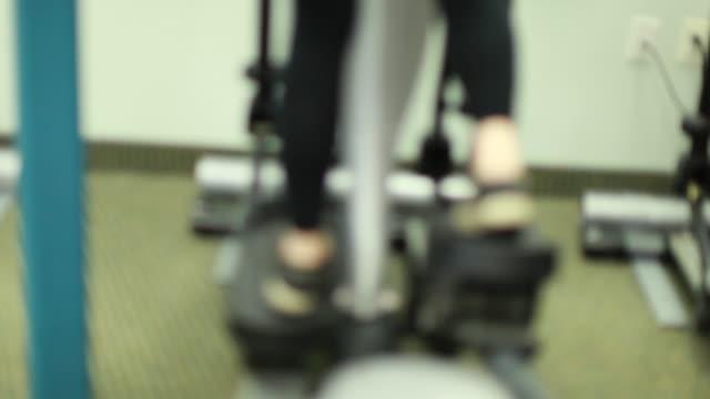 stockvideo's en b-roll-footage met uitoefenen op een elliptische machine - fitnessapparaat