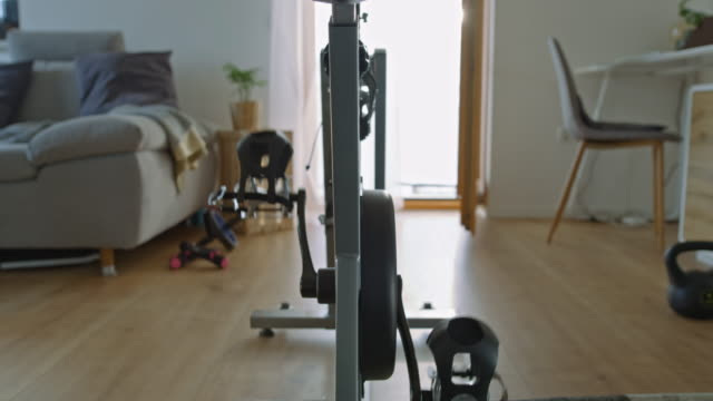slo mo exercising pedals on the exercise bike in a cozy living room - sprzęt sportowy filmów i materiałów b-roll