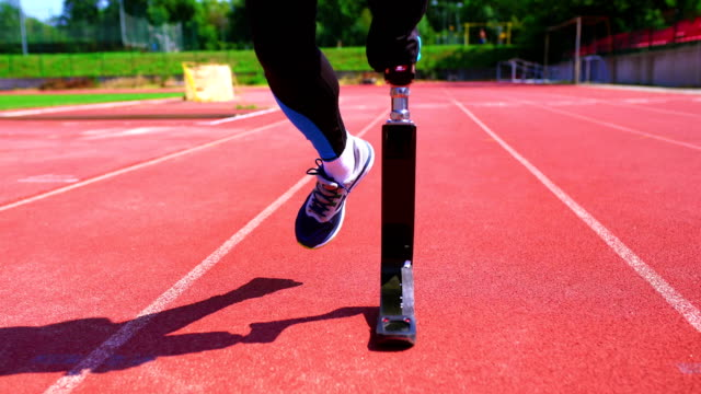 Exercising with prosthetic leg. Closeup front view of mid 20's man with amputated limb and carbon fibre prosthetic limb jogging on a sunny day at a sports track. artificial limb stock videos & royalty-free footage