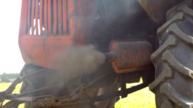 Exhaust pipe of a diesel engine pollutes the air. Close-up of exhaust pipe of old diesel tractor emitting black smoke and particulates. Pollution.