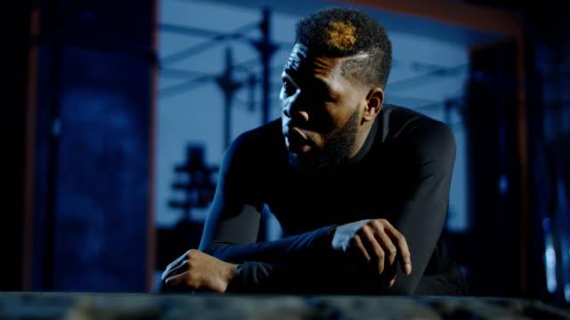 vídeos de stock e filmes b-roll de exhausted black sportsman recovering in gym - dureza