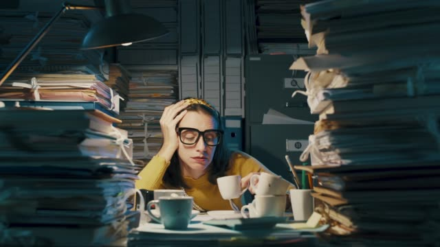 Exhausted bored woman working overtime in the office Exhausted bored woman working until late in the office, she had many cups of coffee and she is overloaded with paperwork large group of objects stock videos & royalty-free footage
