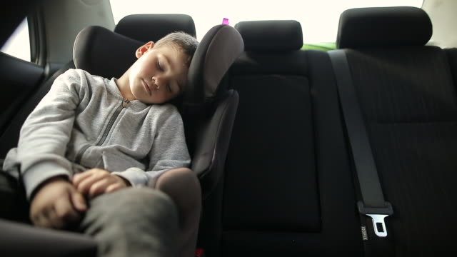 Exhausted boy in car safety seat sleeping during road trip during vacation Exhausted boy in car safety seat sleeping during road trip during vacation one boy only stock videos & royalty-free footage