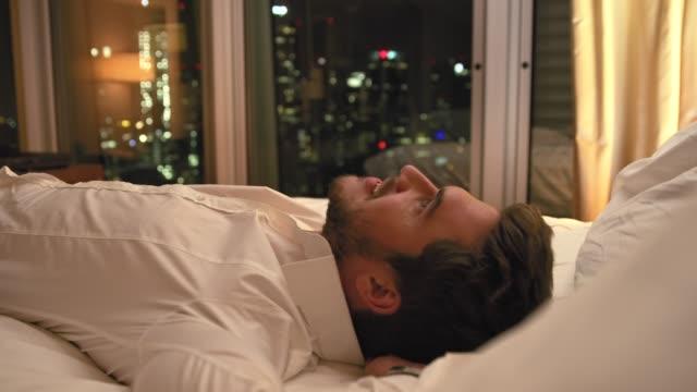 vídeos y material grabado en eventos de stock de hombre de negocios agotado saltando en la cama en la habitación del hotel - acostado