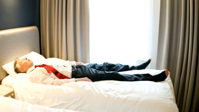 Exhausted businessman lying bed video