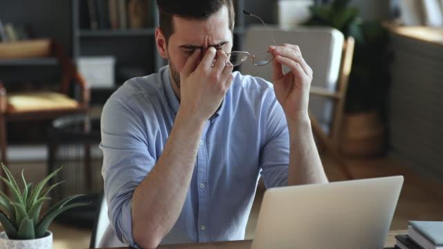 stockvideo's en b-roll-footage met uitgeputte zakenman die glazen afneemt die droge geïrriteerde ogen masseren - overstuur