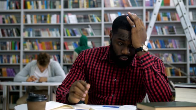 Exhausted dark-skinned student massaging temples Exhausted overwhelmed african american student massaging temples to relieve headache while studying hard in university library. Fatigued college student suffering headache during learning indoors. educational exam stock videos & royalty-free footage