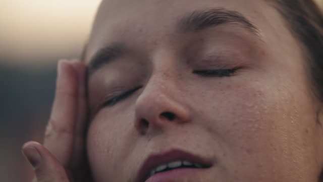 Exhausted female athlete sweating after rowing Slow motion of woman sweating after rowing. Close-up of exhausted young female is taking deep breath. She is wiping face with hand. exhaustion stock videos & royalty-free footage