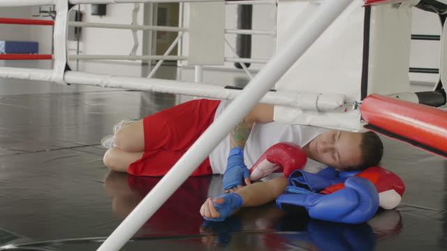 pugile femmina esausto sdraiato sull'anello e con riposo - fragilità video stock e b–roll