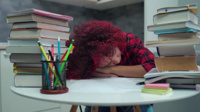 masada uyuyan bitkin kız öğrenci, okul ödevinden bıktı - burnout stok videoları ve detay görüntü çekimi