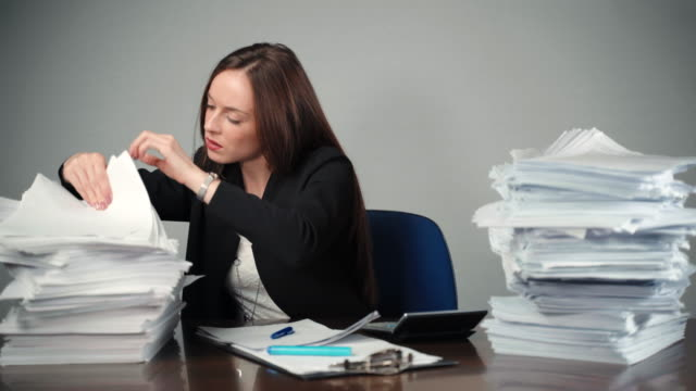 exhausted financial businesswoman doing investment operations in the office room. woman checking a pile of documents and files, comparing data and looking sadly on camera. losing temper at work, overloaded businesswoman concept - modulo documento video stock e b–roll