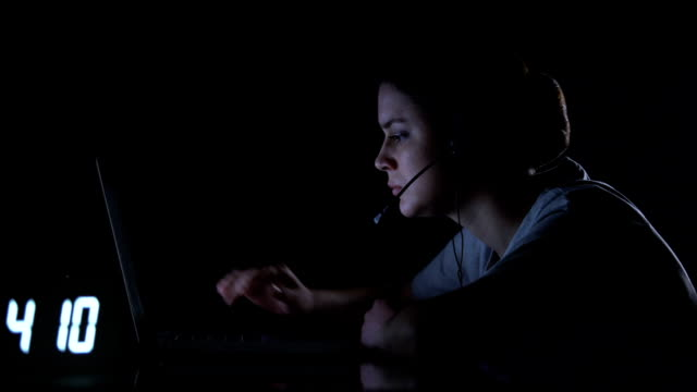 exhausted freelance female closing laptop after night shift, taking off headset - shifts call centre video stock e b–roll