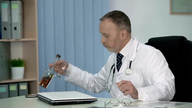 Exhausted male doctor allowing himself strong drink after hard working day video
