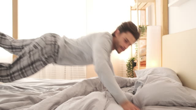 exhausted man jumping on bed to sleep - pajamas stock videos & royalty-free footage