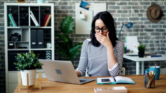 Exhausted office worker using laptop then taking off glasses touching face Exhausted office worker pretty girl is using laptop then taking off glasses touching face feeling tired and stressed. Hard-working youth and stressful job concept. yawning stock videos & royalty-free footage