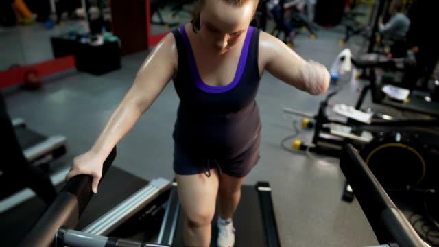 vídeos de stock e filmes b-roll de exhausted overweight woman walking on treadmill, suffering health problems - dureza