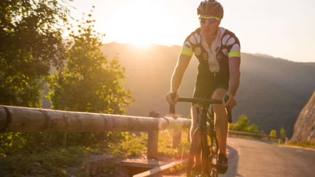 Exhausted road cyclist cycling uphill at sunset video