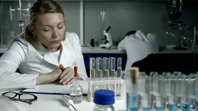 Exhausted scientists sleeping on workplace in lab video
