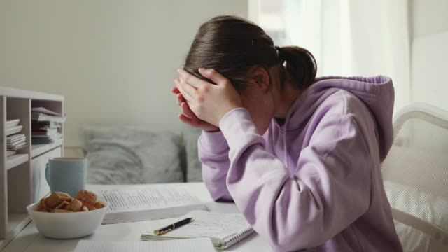 Exhausted upset school girl studying alone feeling headache at home Exhausted or sick upset school student studying alone feeling headache writing difficult assignment at home. Tired depressed bored teenage girl worried about problem in children education concept. educational exam stock videos & royalty-free footage