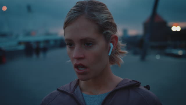 Exhausted woman breathing while using smart watch Close-up of exhausted young woman breathing on footpath against sky. Beautiful athlete is looking away in city. She is using smart watch. sportsperson stock videos & royalty-free footage