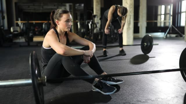 Exhausted women relaxing after workout at gym Handheld shot of exhausted women relaxing by dumbbells. Determined female athletes are taking a break after heavy workout. They are wearing sports clothing. exhaustion stock videos & royalty-free footage