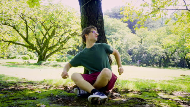Exhausted Young Caucasian Man Sitting Down Below Tree in Park and Admiring Nature Taken in Tokyo, Japan resting stock videos & royalty-free footage