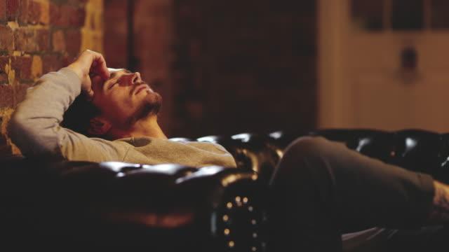 vídeos de stock, filmes e b-roll de ds exausto jovem relaxando em um sofá - sentando