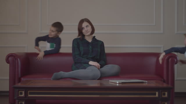 exhausted young mother sitting on home red couch while two loud kids running around the sofa. tired woman has a headache of two noisy boys in the same clothes. - fare la lotta video stock e b–roll