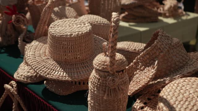 utställning av korgprodukter på gatan. flätade hattar, korgar, handväskor - halmslöjd bildbanksvideor och videomaterial från bakom kulisserna