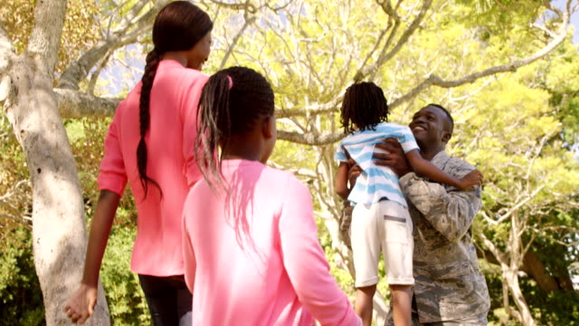 Exited returning soldier man meeting his wife and children video