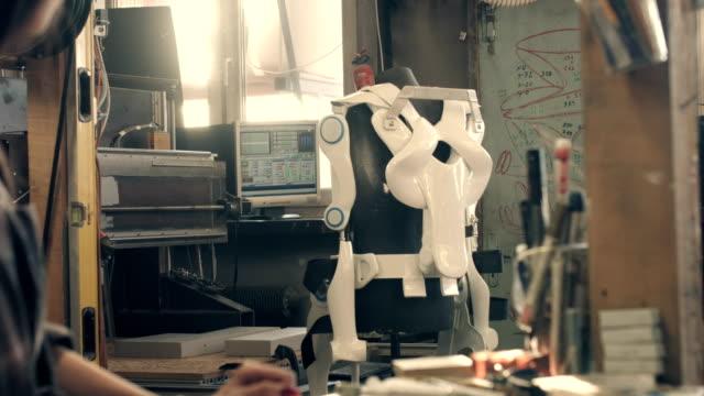 exoskeleton project. woman making last adjustments - манипулятор робота производственное оборудование стоковые видео и кадры b-roll