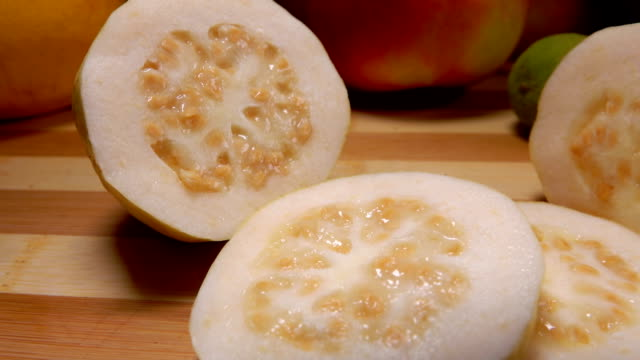 Exotic Guava slices are lying on a bamboo board - video