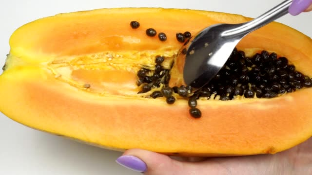 stockvideo's en b-roll-footage met exotische papaya fruit close-up. meisje reinigt zaden van fruit. - tropisch fruit