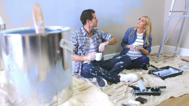 Expectant Couple Taking A Break Whilst Decorating Nursery video