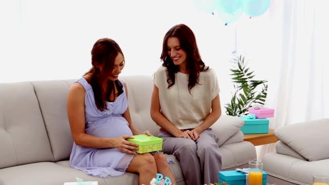 vídeos de stock, filmes e b-roll de mãe grávida abrindo um presente do amigo - chá de bebê