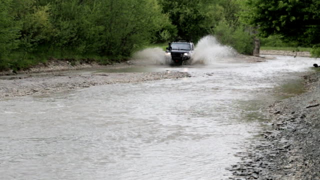 Expeditionary SUV crossing the river with fast speed and splashing video