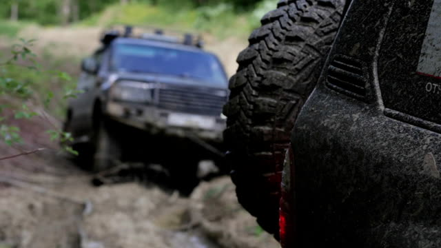 expeditionary suv got stuck in the mud in the forest and get out via another suv - rimorchiatore video stock e b–roll