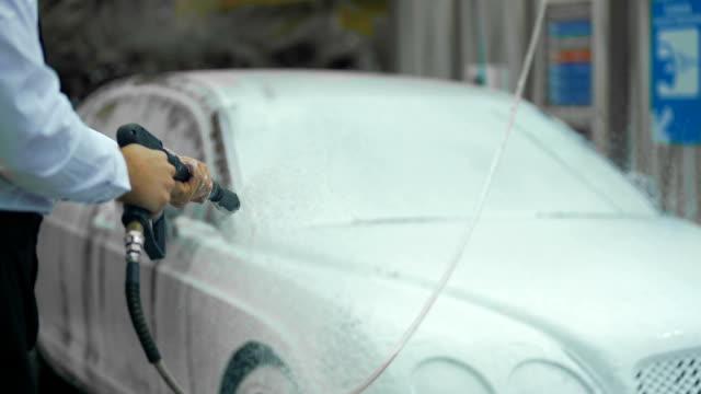 dyra biltvätt, manlig klädd i kostym tvätta bilen med rengöring skum, business - surf garage bildbanksvideor och videomaterial från bakom kulisserna
