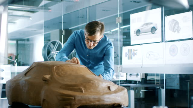 熊手と経験自動車デザイナーを sculpts 粘土粘土から試作車。彼は主要な自動車の本社でモダンなスタジオで動作します。 - 彫刻点の映像素材/bロール