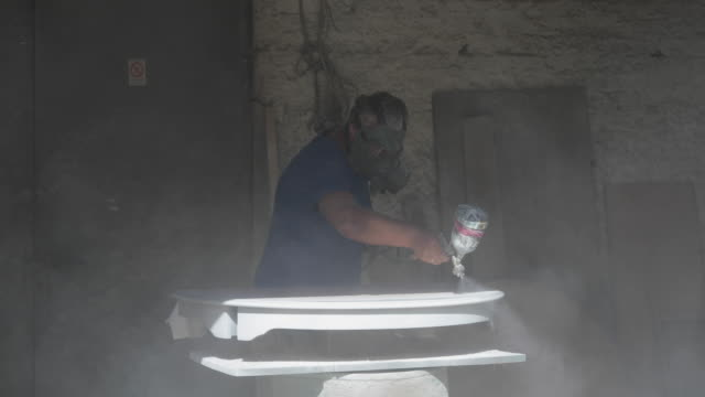 Experienced carpenter in casual clothes with gas mask on and small buiness owner paints a wooden furniture in white color in workshop