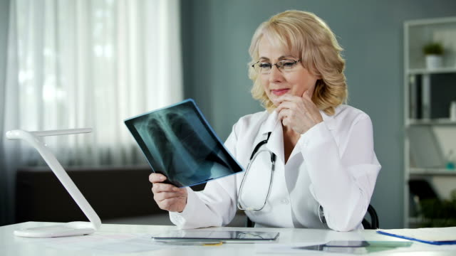 Experienced female radiologist studying X-ray picture, qualified diagnostics video