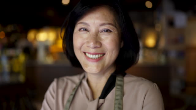 Experienced In Running Her Business Portrait of a senior Asian woman standing at the cafe she owns. owner stock videos & royalty-free footage