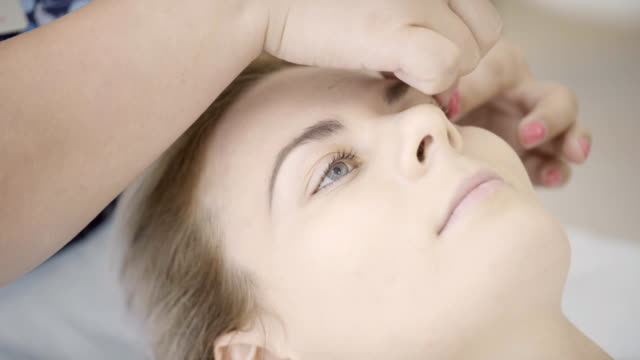 Experienced masseur makes forehead eyebrows massage of lying woman in spa salon indoors video